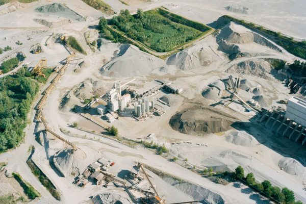 """Aerial view of an extractive area in Montichiari. The presence of these huge quarries to be filled has given rise to the impressive waste business. Toxic waste from many foreign countries, including former USSR members and Australia, was found in both authorized and illegal landfills (https://espresso.repubblica.it/plus/articoli/2020/06/10/news/brescia-vuole-guarire-anche-dal-cancro-1.349238). """"Thirty-five years ago our territory was a typical plain one; a smooth, flat territory. It was a territory where wheat was grown. This is why since ancient times our villages in this area have been called Fascia d'Oro, the gold of wheat spikes; Vighizzolo, alley of the sun: the sun, the wheat illuminated by the light"""" - says Luciano Gerlegni, president of Legambiente committee in Montichiari. The photo was taken from a small airplane with my analog camera."""